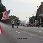 Early runners approach American Flags at the Peachtree Road Race in Atlanta